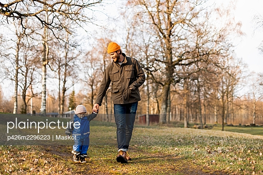 Full length of father and son holding hands while walking at park - p426m2296223 by Maskot