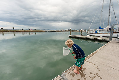 Preschooler with net standing on a dock near water - p1166m2124114 by Cavan Images