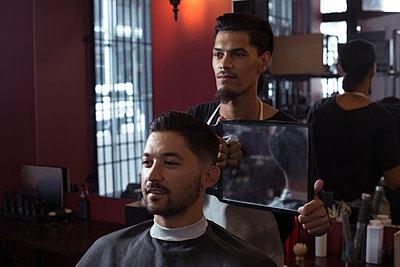 Man looking his new hair cut in the mirror - p1315m1579063 by Wavebreak