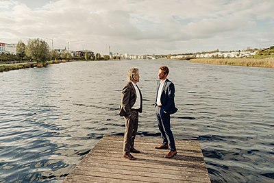 Two businessmen standing on jetty at a lake talking - p300m1535873 by Kniel Synnatzschke