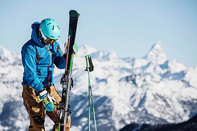 Skier preparing to put on skis - p429m1519420 by Guido Cavallini