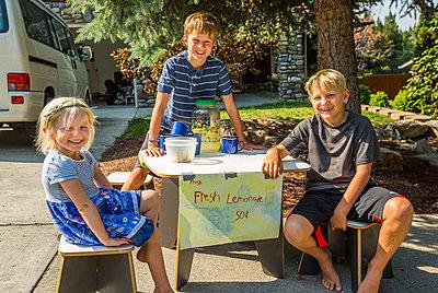 Smiling Caucasian boys and girl selling lemonade - p555m1303704 by Steve Smith