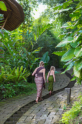 Mother and children walking along stone path - p555m1419667 by Marc Romanelli