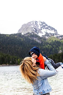 Mother kissing her babyboy at a lake in the mountains - p795m2168554 by JanJasperKlein