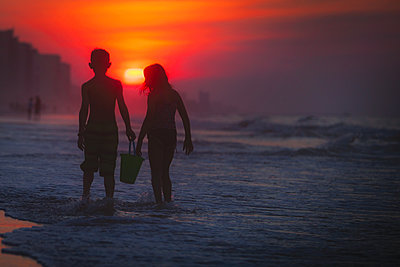 Siblings paddling in sea at sunset, North Myrtle Beach, South Carolina, United States - p924m1506713 by Rebecca Nelson