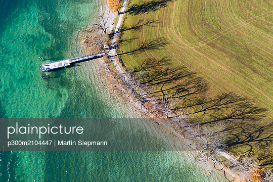 Germany, Bavaria, Kaltenbrunn, Tegernsee, shadows of trees at the lakeshore and jetty, aerial view - p300m2104447 by Martin Siepmann