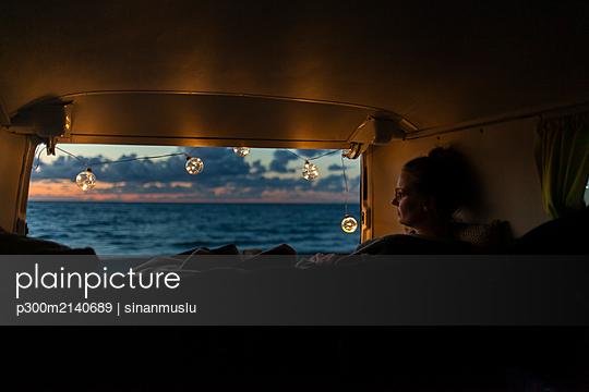 Woman in a van looking sideways at sunset - p300m2140689 by sinanmuslu