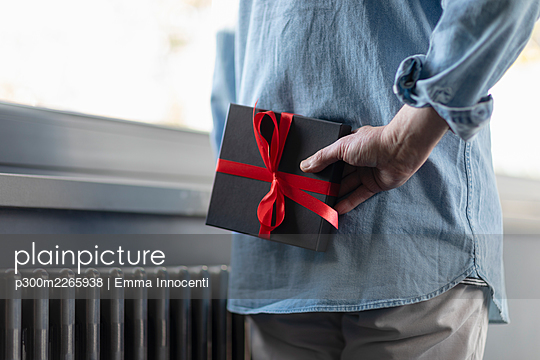 Man holding gift box behind while standing at home - p300m2265938 by Emma Innocenti