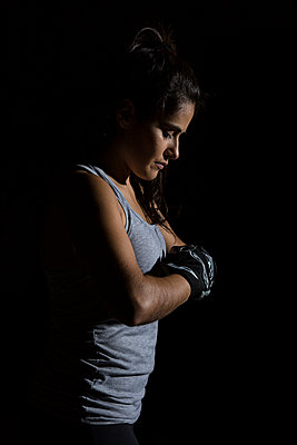 Portrait with black background of woman in gym with boxing gloves - p1166m2123618 by Cavan Images