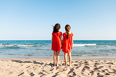 Back view of two little sisters standing at waterside on the beach looking to the sea - p300m1157299 by Valentina Barreto