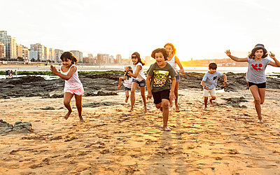 Kids running on the beach at sunset - p300m1175672 by Marco Govel