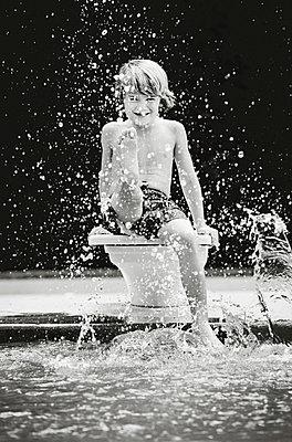 Portrait playful boy splashing water at swimming pool - p301m2202374 by Tamara Lackey
