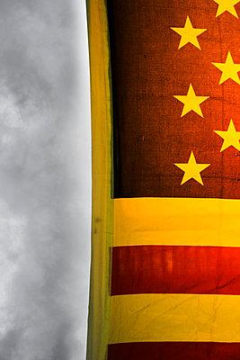 American flag against dark clouds - p975m2286081 by Hayden Verry