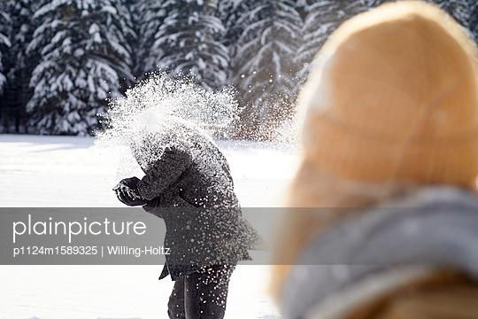 Junges Paar macht eine Schneeballschlacht - p1124m1589325 von Willing-Holtz