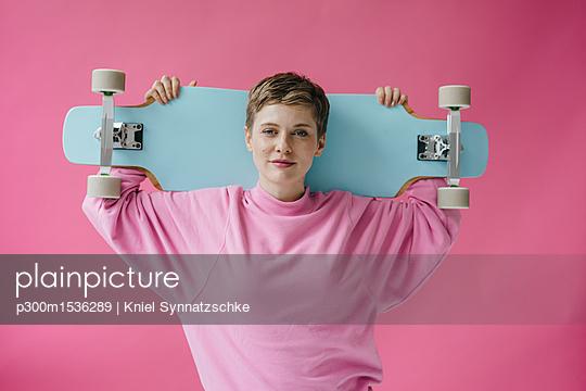 Portrait of woman in pink holding skateboard - p300m1536289 by Kniel Synnatzschke