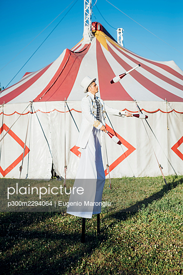 Male artist juggling pins while standing with stilts on meadow - p300m2294064 by Eugenio Marongiu