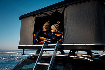 Siblings looking away while sitting in roof tent on car - p1166m1543190 by Cavan Images