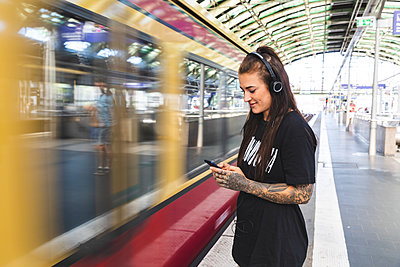 Tattooed young woman with headphones standing at platform using smartphone, Berlin, Germany - p300m2156860 by William Perugini