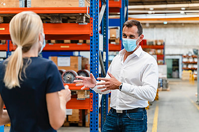 Businessman discussing with female colleague while standing in factory during COVID-19 - p300m2240112 by Daniel Ingold