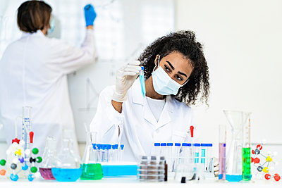 Female researcher examining liquid in test tube while coworker working in background at laboratory - p300m2265534 by Giorgio Fochesato