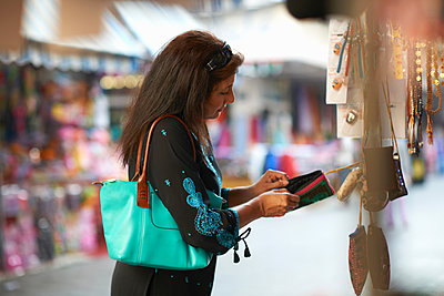 Mature female tourist looking beaded purse on market stall, Sharjah, United Arab Emirates - p429m1408048 by Peter Muller