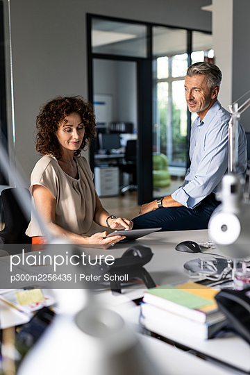 Mature businesswoman explaining over digital tablet to colleague while sitting at office - p300m2256435 by Peter Scholl