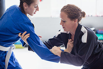 Focused women practicing judo in gym - p1023m1506459 by Sam Edwards