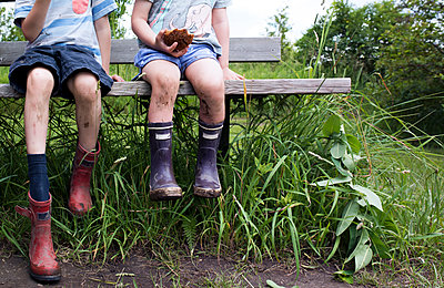Low section of siblings wearing messy boots while sitting on bench at field - p1166m1486304 by Cavan Images