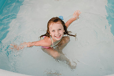 Portrait of a happy girl in an inflatable swimming pool - p300m2206979 by Sara Monika