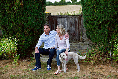 Romantic mature couple with dog sitting in garden - p429m2032222 by Image Source