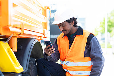 Male engineer standing next to yellow truck looking at smartphone - p429m2138634 by Sigrid Gombert