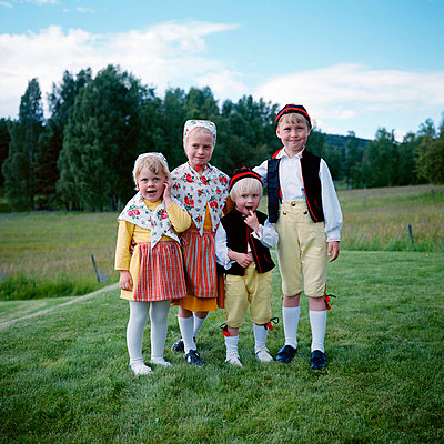 Children in traditional clothing standing on grass field, portrait - p528m672591 by Johan Willner