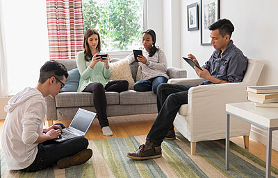 Friends using technology in living room - p555m1413024 by JGI/Tom Grill