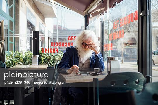 Senior businessman using digital tablet in cafe, Milano, Lombardia, Italy - p429m2091346 by Eugenio Marongiu