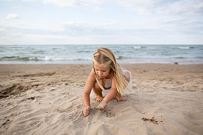 Full length of girl playing on sand at beach - p1166m2040326 by Cavan Images