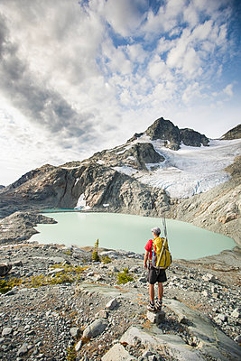 Backpacker stops to look at view of mountains glacier and lake. - p1166m2162475 by Cavan Images