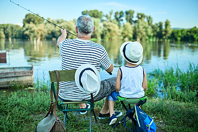 Back view of grandfather and grandson fishing at lakeshore - p300m2023604 by Zeljko Dangubic