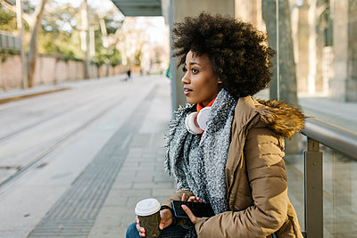 Afro woman with smart phone and disposable coffee cup contemplating at bus station during winter - p300m2257487 by Xavier Lorenzo