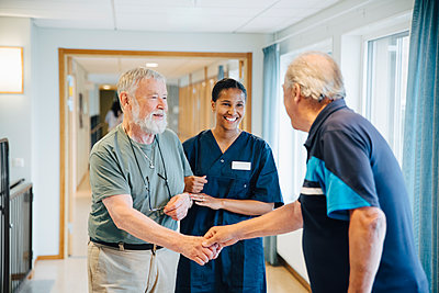 Senior man arm in arm with female nurse while giving friend handshake in alley at nursing home - p426m2149325 by Maskot