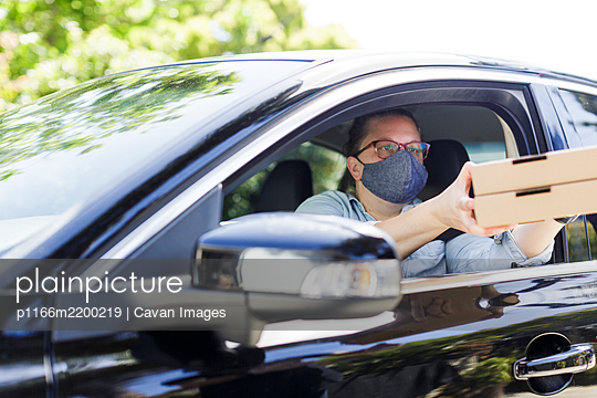 Woman picks up pizza while wearing mask - p1166m2200219 by Cavan Images