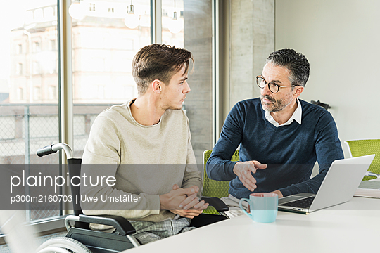 Mature businessman and young man in wheelchair talking at desk in office - p300m2160703 by Uwe Umstätter