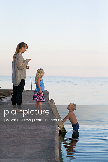 Mother with children on pier - p312m1229288 by Peter Rutherhagen