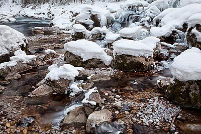 Fließendes Wasser eines Baches mit Schnee und Eis über den Steinen - p1383m1444550 von Wolfgang Steiner