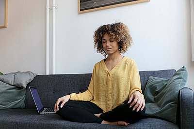 Young woman sitting on couch at home next to laptop meditating - p300m1536030 by harry + lidy