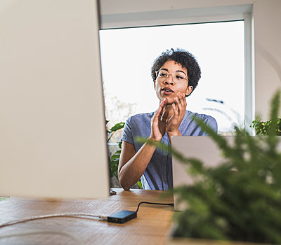 Woman sitting in front of computer, having video conference - p300m2243496 by Uwe Umstätter