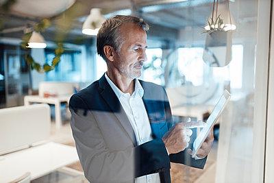 Senior businessman using digital tablet in office - p300m2287454 by Gustafsson