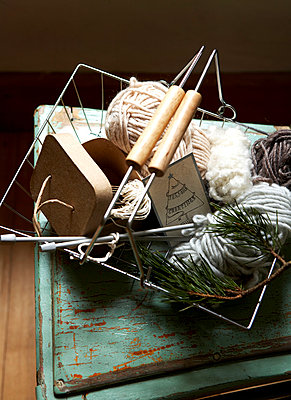 Variety of wools with knitting needles in wire basket;  Isle of Wight;  UK - p349m920059 by Rachel Whiting