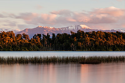 Mountains over forest and still river, Hokitika, South Westland, New Zealand - p555m1410104 by Jeremy Woodhouse