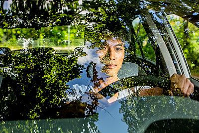 Young man at the steering wheel of car - p975m2207628 by Hayden Verry