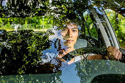 Junger Mann am Lenkrad eines Autos - p975m2207628 von Hayden Verry